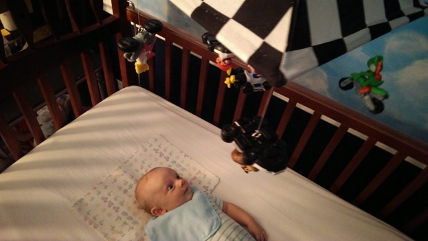 Baby is transfixed with his Mario Kart mobile in his very own Mario themed nursery bedroom